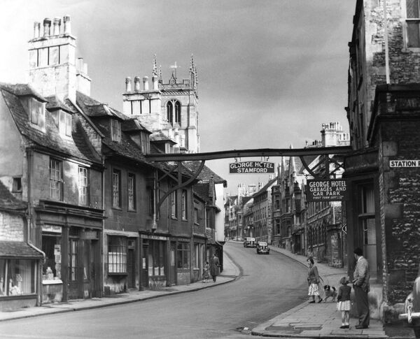 A huge sign spanning the street advertises the George Hotel, in the historic town of Stamford, Lincolnshire, England. Date: 1950s
