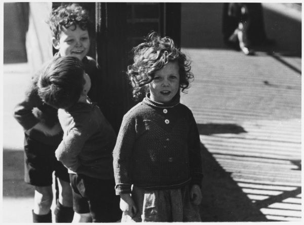 A little girl and two boys standing in the street