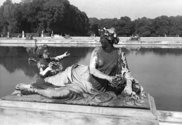 Close-up of a statue at the side of a stretch of water in the grounds of the Palace of Versailles, near Paris, France. Date: 1961