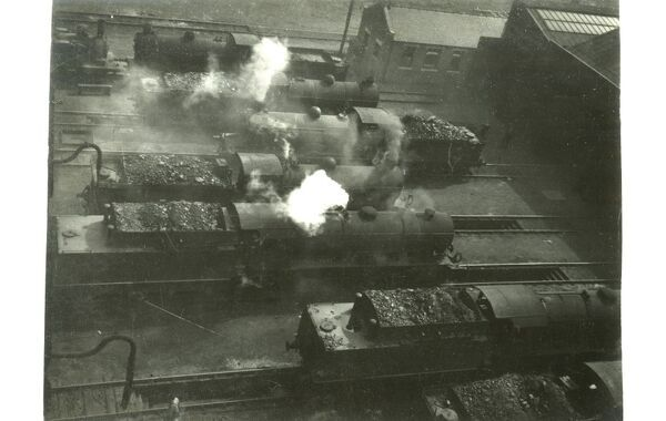 An aerial view looking down on a group of working steam locomotive some entering and someexiting their shed. From the collection of a Scottish rail accident investigator
