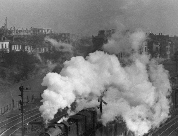 A train leaves Euston Station for the north, filling the atmosphere with a large plume of white steam