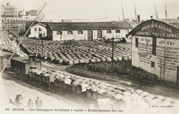 The steamship harbour at Algiers - the wine export section. Thousands of barrels of wine awaiting transportation to Europe. The barrels are brought to the Quayside in the railway carriages, which can be seen in the foreground
