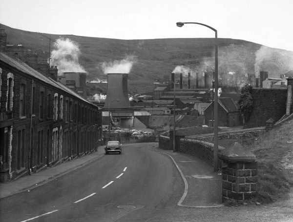 A view looking down a road in Wales with the smoking chimneys of a steelworks in the background. Date: 1974