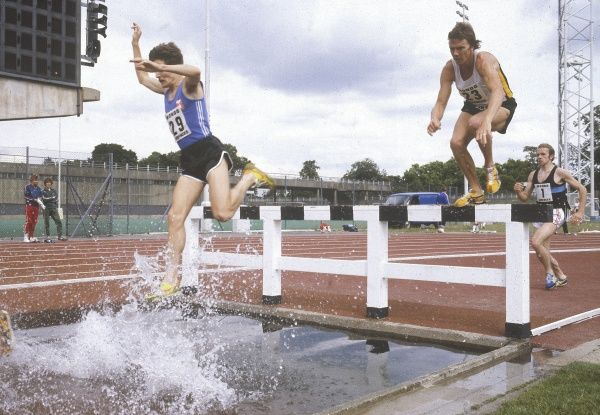 Athletes negotiating a Steeplechase Water Jump hurdle. Date: 1980