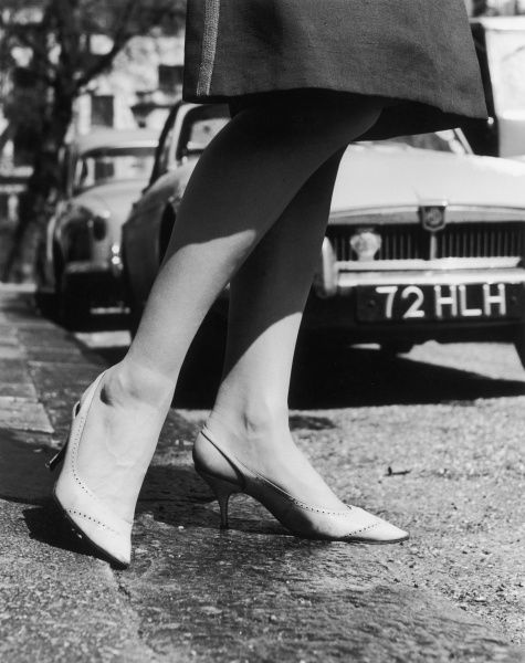 A close-up picture of a woman's legs stepping off a curb in a pair of high heeled shoes