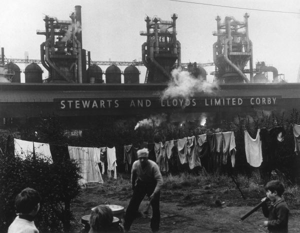 An old man and children in a back garden, washing hanging on the line, and the smoking factory chimneys of Stewarts and Lloyds in the background. Date: 1950s