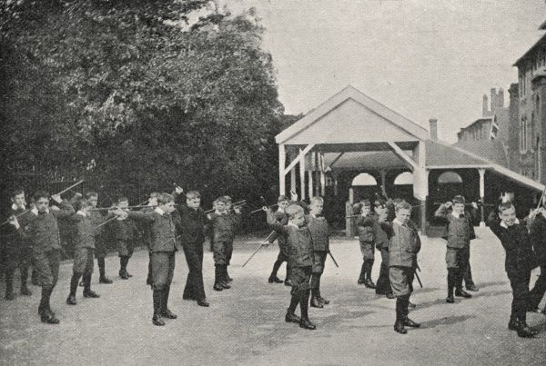 Boys perform an exercise known as stick drill at the Lambeth Schools for workhouse children on Elder Road, West Norwood, South London. They are all wearing identical uniform. A young Charlie Chaplin was briefly a resident of the Schools in 1898