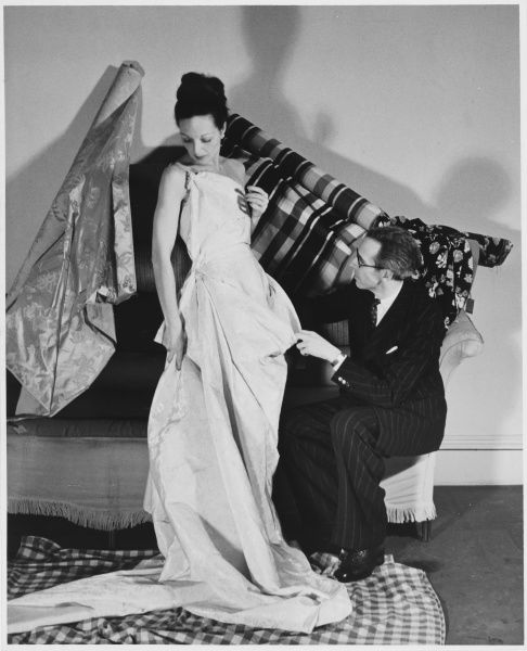 Fashion designer Victor Stiebel (1907-1976) photographed fitting the model Peggy Meredith