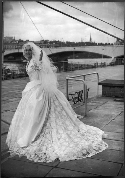 A wedding dress by Victor Stiebel (1907-1976) worn by a model who poses on the South Bank outside the newly built Royal Festival Hall in London
