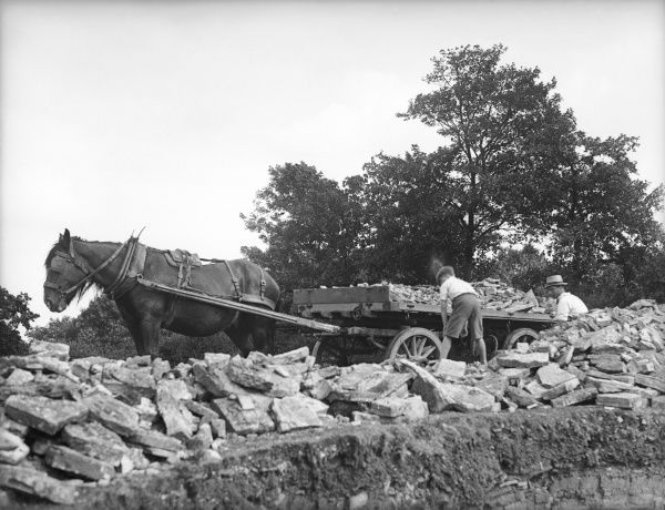 Men loading stone slabs onto a horse-drawn cart at a stone quarry