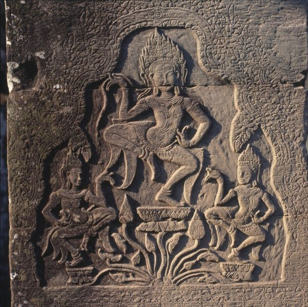 A stone relief carving at the entrance to the Wat Bayon Khmer Buddhist temple at Angkor Thom, Siem Reap, Cambodia, built in the late 12th and early 13th centuries. The carving depicts three dancers holding lotus blossoms