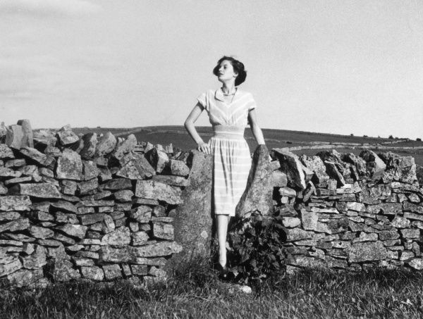A country girl stops to take a breath of fresh country air as she climbs over a stile in a dry stone wall. Date: 1950s