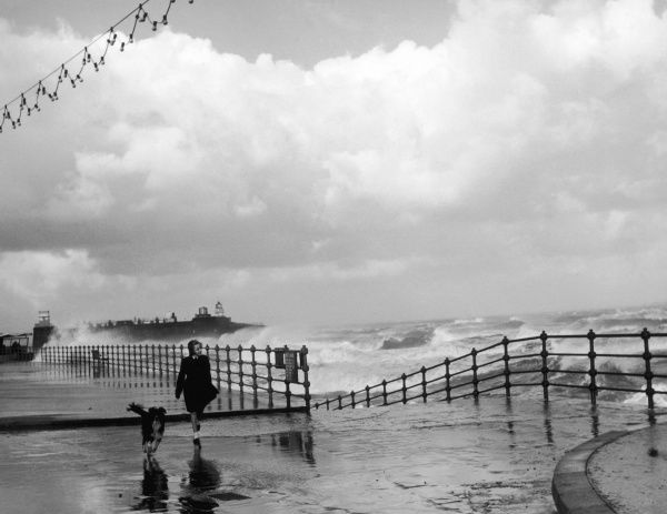 A schoolgirl and her dog enjoy the rough sea and stormy weather at New Brighton, Cheshire, England