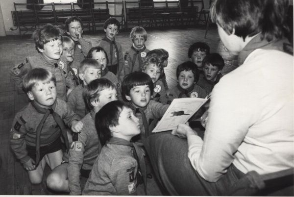 A group of Irish Beaver Scouts sit on the floor looking up at their leader who shows them pictures from 'The Story of the Beaver' book