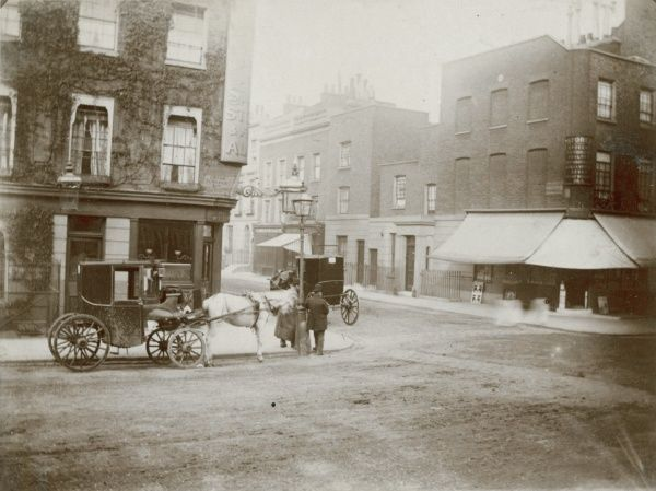 The corner of Eaton Terrace and Chester Row, London. A two horse-drawn carriage and two men stand by a lamppost. The building on the corner is the Duke of Wellington pub (still there today) - perhaps the driver of the carriage waiting outside is in there