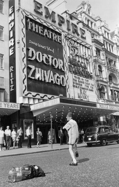 A street entertainer performs a trick involving a tartan bag and a wooden box, much to the amusement of the tourists in Leicester Square, where Doctor Zhivago is on at the cinema! Date: 1966