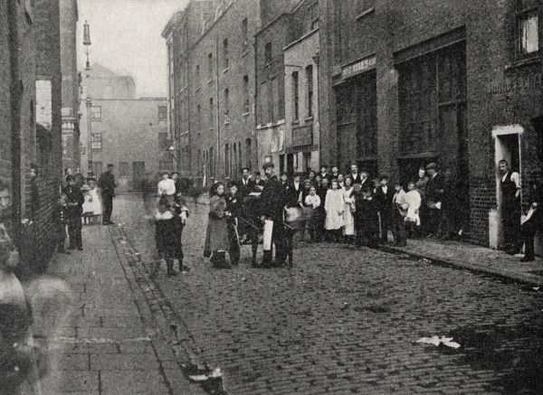 A street scene in Hoxton, East London. A large group of local residents are lined up for the occasion. The location may be Boot Street, adjacent to Hoxton Market