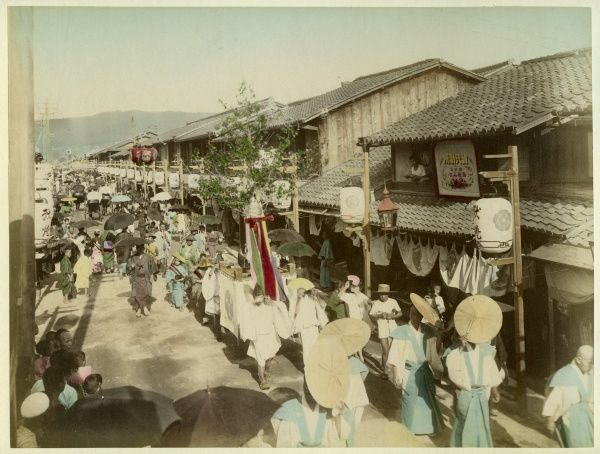 A busy street in a Japanese town or village; parasols and umbrellas are in evidence