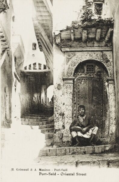 Delightful photographic street Scene in Port Said, Egypt with a young man seated in an elaborate ornate doorway alongside a thin winding stair leading up into the town