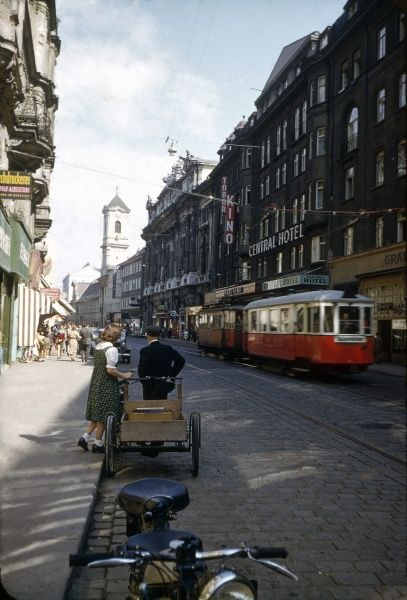 View of a street in Vienna, Austria, with a red and white tram on the right, in front of the Central Hotel. Date: 1953