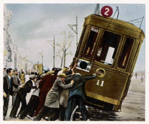 A crowd of people try to overturn a tram during a general strike and rioting in Valencia