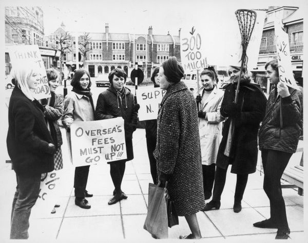 An pensioner takes time out from her shopping trip to read the banners of the a group of female students, who are protesting against a rise in student tuition fees. Date: 1960s
