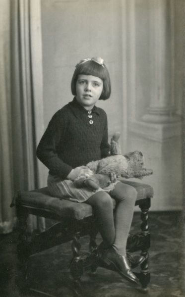 A little girl poses with her teddy bear in the photographer's studio. Date: circa 1940