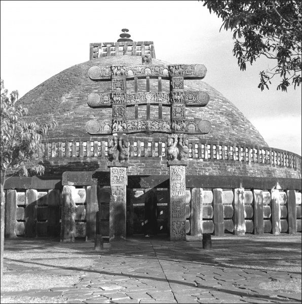 The Stupa at Sanchi, Madhya Pradesh Province, Central India, with an ornately carved gateway at the entrance. The Stupa is a large hemispherical dome with a central chamber containing relics of the Buddha. Photograph by Ralph Ponsonby Watts