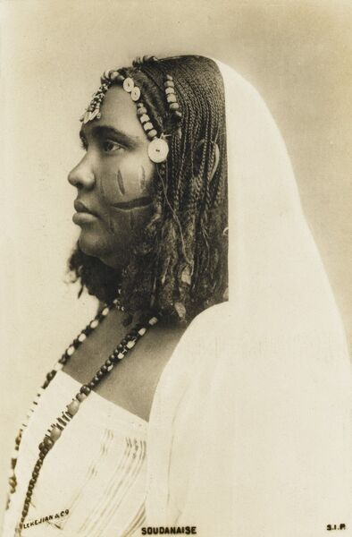 Sudanese woman with traditional decorative cuts on her face, braided hair (with buttons and beads) and long beaded necklace