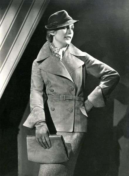 Stylish double-breasted, belted, suede jacket with large pointed collar & revers & pocket flaps. Worn with matching gauntlets & clutch handbag. Date: 1930s