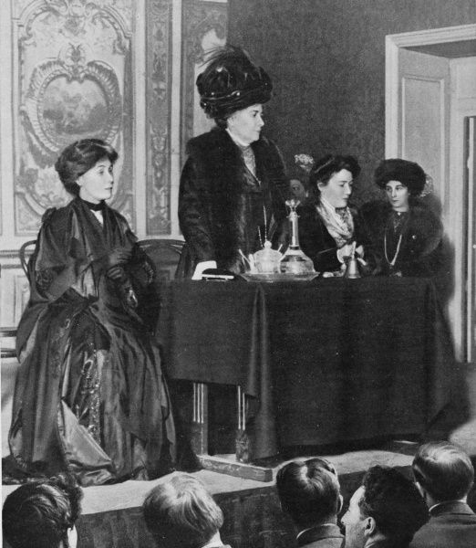 Emmeline Pankhurst (seated on left) and her secretary (miss Lawrence) visit their French sisters to compare notes : Mme Schmahl welcomes them at a Paris meeting