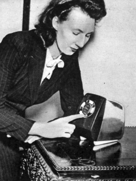 Photograph of a woman demonstrating an electric toaster with adjustable dial at the Olympia Ideal Home exhibition 1947