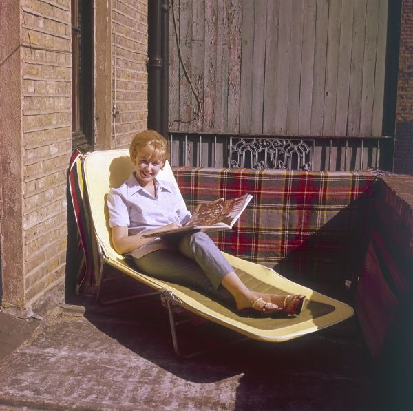 A happy blonde woman, flipping through a magazine, whilst sunbathing on her patio sun lounger! Date: 1960s