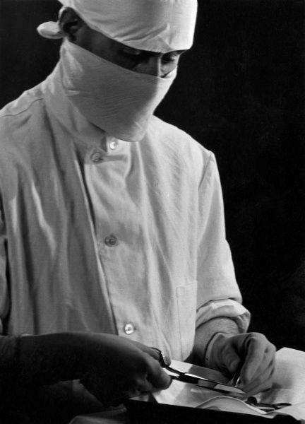 A surgeon cuts the surgical wire with his scissors following a successful operation. Date: 1930s