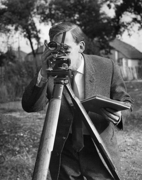 A surveyor at work with a theodolite level