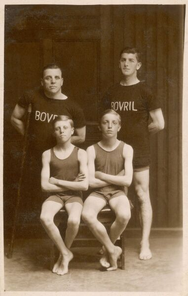 Four swimmers pose for their photograph. The two men are wearing Bovril teeshirts, while the two boys wear one-piece swimming costumes