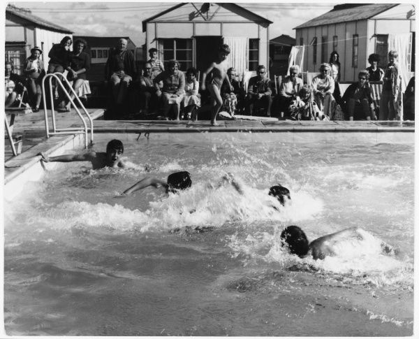 Four young boys compete against one another in a swimming race at a holiday camp, while proud parents watch on deckchairs outside their chalets
