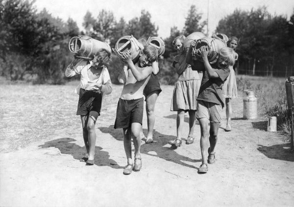 Teamwork! Boys and girls carrying heavy milk churns on their shoulders at a summer holiday camp in Switzerland. Date: 1930s
