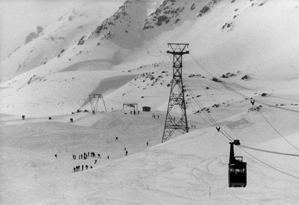A scene showing a cable car, skiers and the ski lift, Switzerland.  1960s