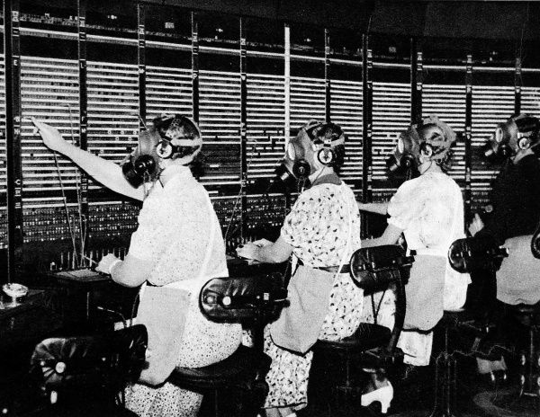 Photograph showing switchboard operators in Faraday Building, City, London, wearing special gas-masks with ear-phones and mouthpieces; a precautionary, anti-air-raid measure in the event of a gas attack