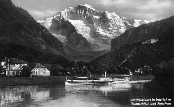 Splendid view of Interlaken, Switzerland - A boat trip heads off onto the lake, with the Heimwehfluh Hill and the Jungfrau Mountain in the background. Date: circa 1920s