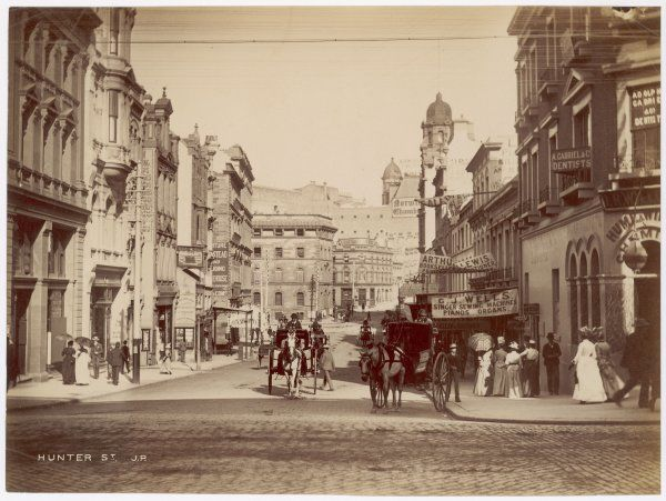 A street scene in Sydney showing shop signs, pedestrians and horse carriages