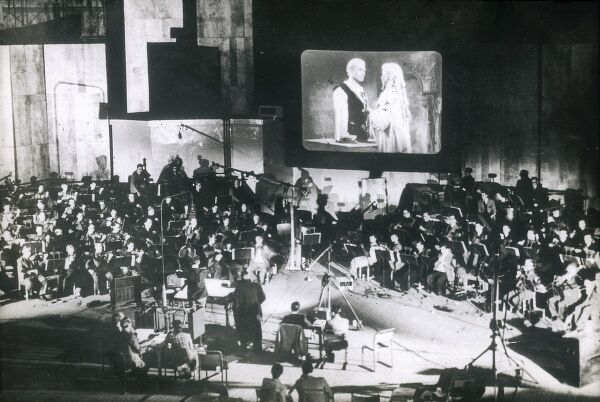 A live orchestra synchronizing music and sound to a film screen. Date: circa 1930
