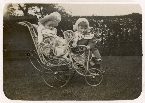 Two children in a tandem-style pram