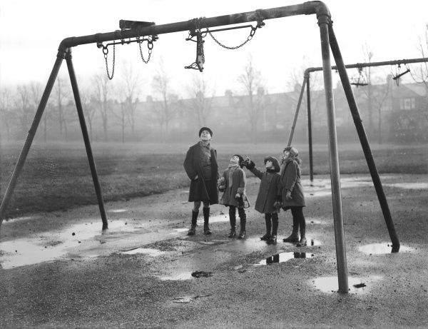 A group of children in a playground on a wet day, wondering how to get the swings untangled! Date: early 1930s