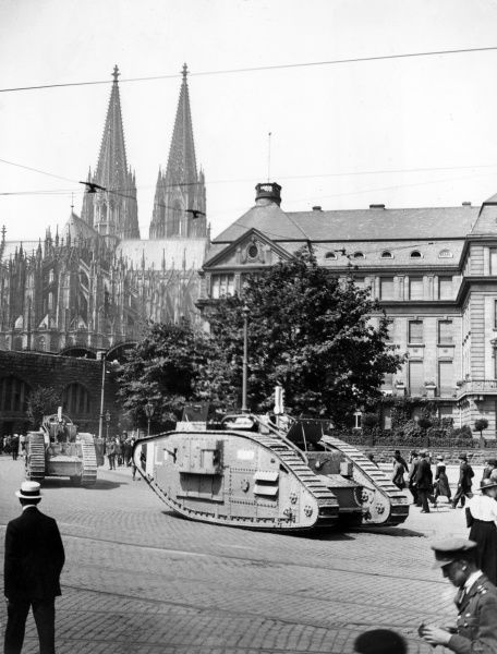 Two tanks moving through a street in Cologne, Germany, with the Cathedral in the background. The tanks are preceded by a guard of the Royal Navy, ready for an inspection by the VI Corps Commander. Date: June 1919