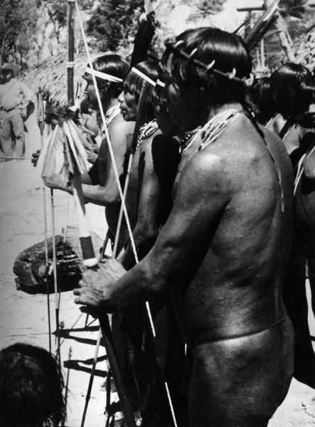 Tapirape warriors of Brazil, South America, at the annual ceremonial dances. The magician in the foreground is wearing a very rare crown of Black Jaguar claws. Date: 1930s