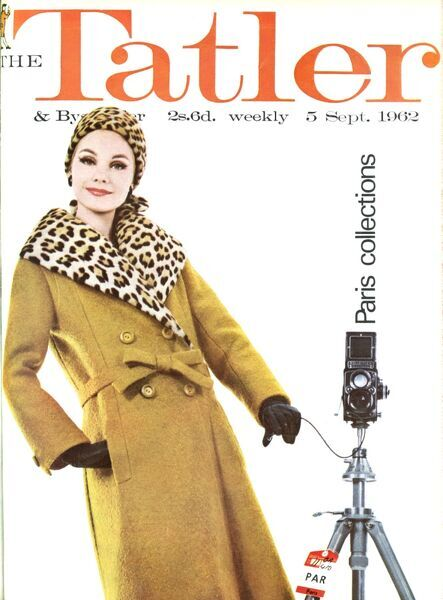A model poses with a camera poised on the front cover of The Tatler special edition about the new Paris collections, wearing a mustard frieze tweed coat with a bow belt and matching dress by Christian Dior. The collar and hat are of ocelot fur