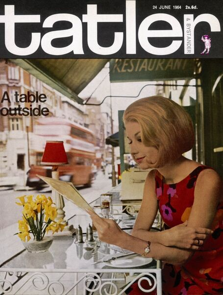 A colour photograph on the front cover of The Tatler and Bystander, depicting a lady reading a menu with busy road behind her