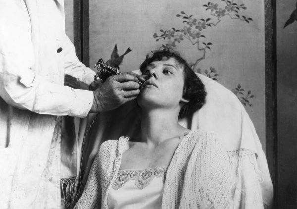 The latest craze for feminine beauty is the tattooing of the lips with small flowers and butterflies. This picture shows a lady being tattooed in a West End (of London) salon. Date: 1929